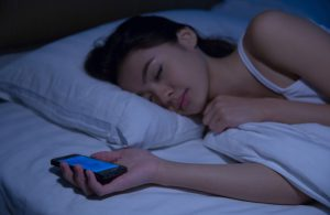 Girl asleep in bed with mobile phone